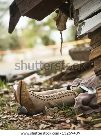 Wicked witch of the west (from the Wizard of Oz) sticking out from under house destroyed by a tornado. - stock photo