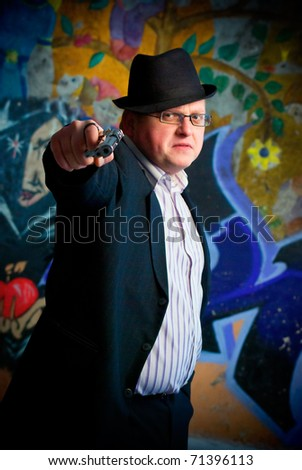 wicked young man aiming with pistol on graffiti background - stock photo
