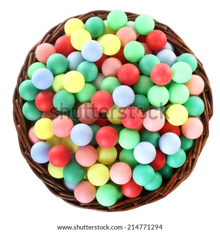 Wicker basket full of colorful balls - stock photo