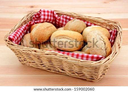 Wicker basket full of crusty bread rolls on a wooden table - stock photo