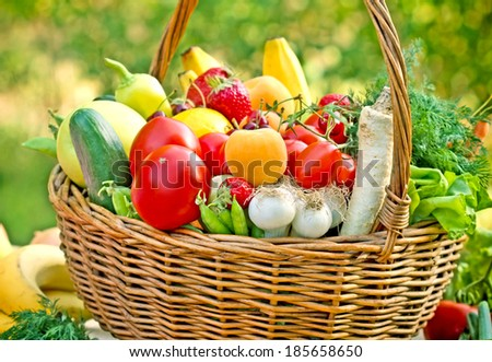 Wicker basket full of fruits and vegetables - stock photo