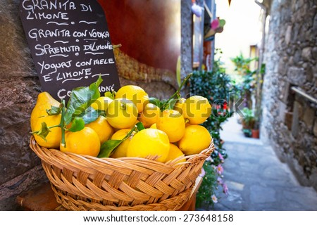 Wicker basket full of lemons on the italian street od Corniglia - stock photo