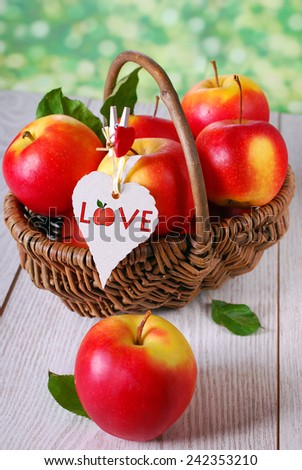 wicker basket full of red apples with hanging eco paper tag on wooden table in the garden  - stock photo