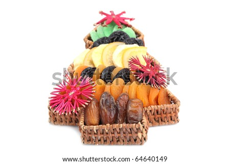 Wicker basket in the shape of Christmas tree with variety of dried fruits isolated on white background. Shallow dof - stock photo
