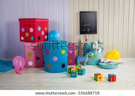 Wicker basket of colored storage and toys - stock photo