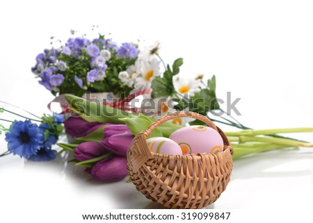 wicker basket of easter eggs with flowers