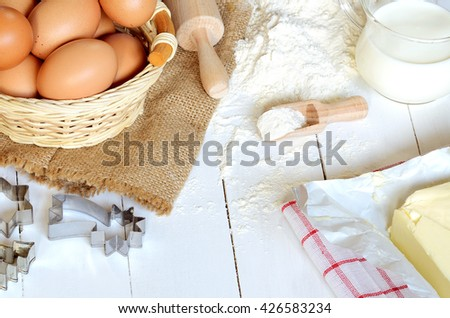 Wicker basket of eggs, heap of flour, glass of milk, rolling pin, butter and cake molds on white wooden desk - baking