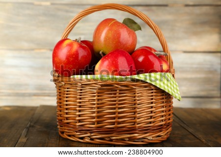 Wicker basket of red apples with green napkin on table and wooden background - stock photo