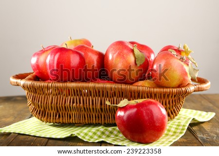 Wicker basket of red apples with napkin on wooden table, on light background - stock photo
