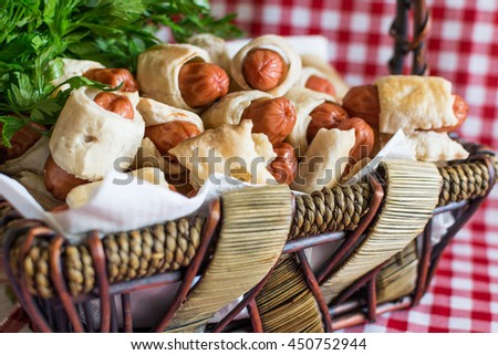 Wicker basket with artisan mini hot dogs (Sausage in the dough) close-up on a plaid background - stock photo
