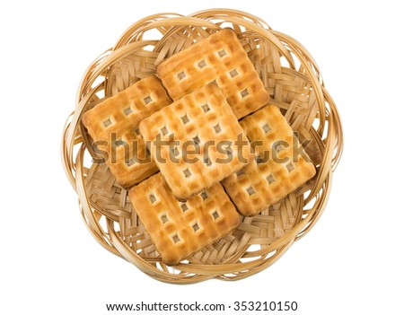 Wicker basket with biscuits sandwiches isolated on white background, top view