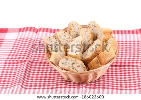 Wicker basket with bread slices on tablecloth. Whole background. - stock photo