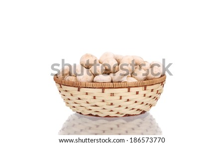 Wicker basket with champignon mushrooms. Isolated on a white background. - stock photo
