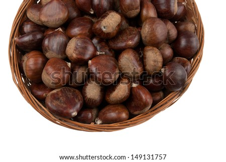 Wicker basket with chestnuts isolated on white background.