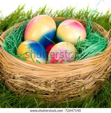 Wicker basket with Easter eggs on green grass.