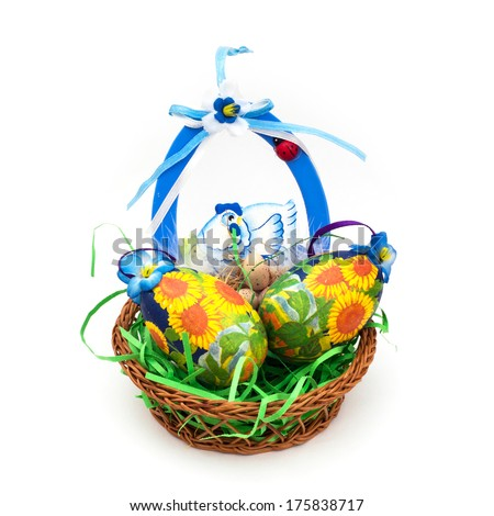 Wicker basket with easter painted eggs on a white background.