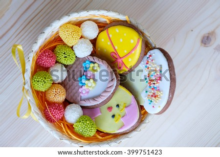 wicker basket with Easter sweets on wooden table