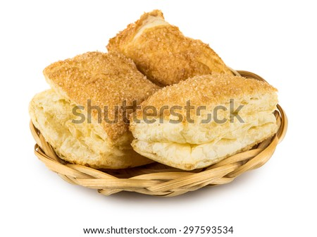 Wicker basket with flaky biscuits isolated on white background - stock photo