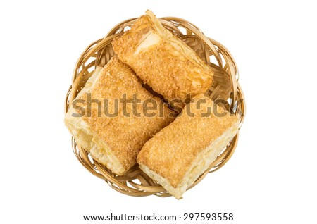 Wicker basket with flaky biscuits isolated on white background, top view - stock photo