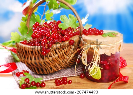 wicker basket with fresh red currant and jar of homemade preserve on wooden garden table