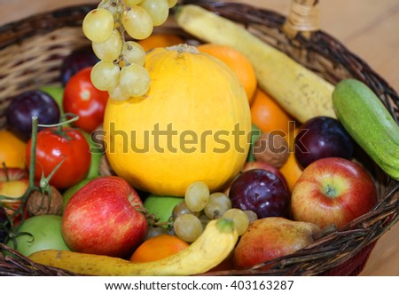 wicker basket with lots of fresh fruit in autumn and winter season