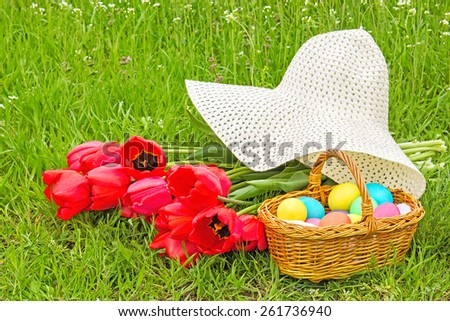 Wicker basket with painted Easter eggs, red tulips and white hat on green spring lawn - stock photo