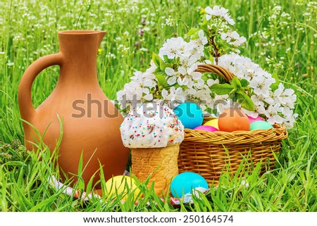 Wicker basket with painted eggs, Easter cakes, a clay jug and flowering branch cherry on spring green meadow