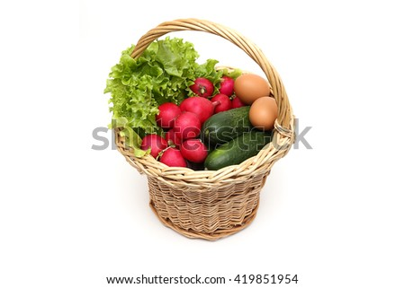 Wicker basket with radish , cucumber , lettuce and chicken eggs on a white background