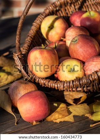 Wicker basket with red apples on a wooden table.