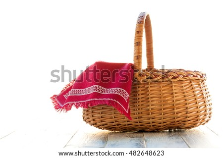 Wicker basket with red napkin on a wooden table, close-up, natural background