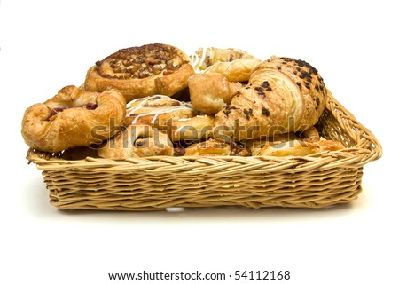 Wicker basket with selection of French & Danish pastries on white background.