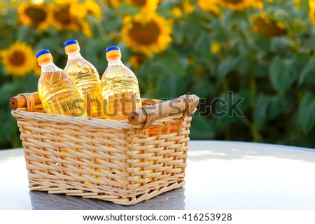 Wicker basket with three bottles of sunflower oil on the background of the field.Backlight. - stock photo