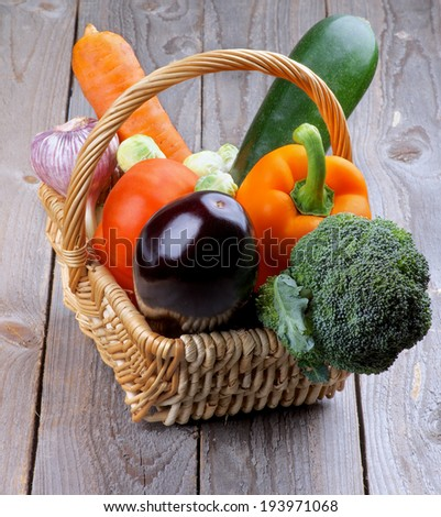 Wicker Basket with Various Colorful Ripe Raw Vegetables closeup on Rustic Wooden background - stock photo