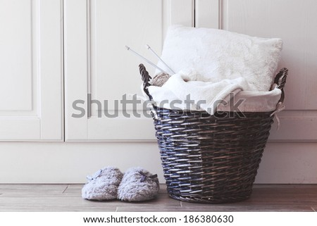 Wicker basket with warm blanket and knitting in it and soft slippers near it - stock photo