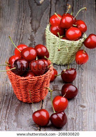 Wicker Baskets with Ripe Sweet Cherries isolated on Rustic Wooden background - stock photo