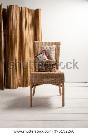 wicker chair and wicker screen with pillow wicker basket - stock photo