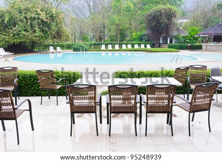 Wicker chair beside the pool at the natural hotel. - stock photo