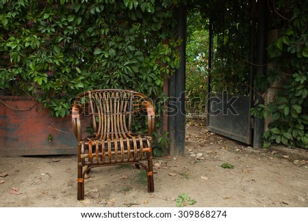 Wicker chair in a garden. Brown wicker chair outside. Old empty wooden chair in the park - stock photo