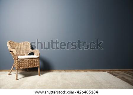 Wicker chair on dark grey wall background - stock photo
