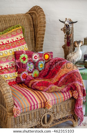 wicker chair with colorful rugs