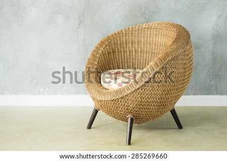 wicker chair with cushion on tile floor with cement plaster wall - stock photo
