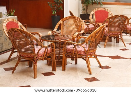Wicker chairs and a round table in the lobby, close-up. horizontal