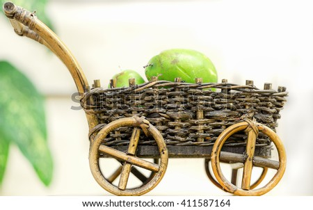 Wicker decorative cart with fruits on white background - stock photo