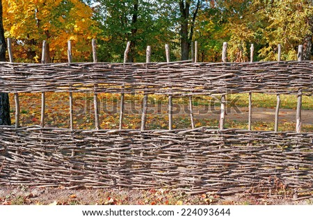 Wicker fence against the backdrop of autumn trees                                - stock photo