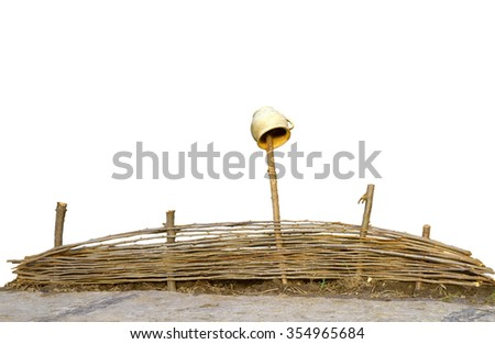 Wicker fence of thin rods with old clay pot hanging to dry on a wooden column isolated on white background with clipping path  - stock photo
