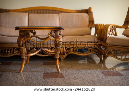 Wicker furniture table in the interior. - stock photo