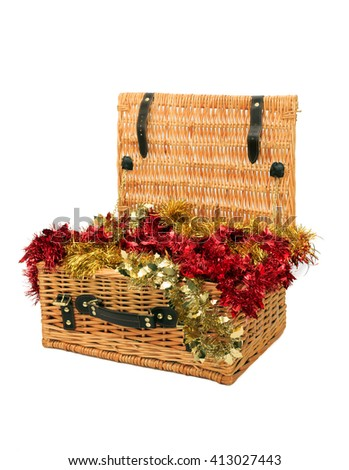 wicker hamper filled with red and gold tinsel garlands isolated on white