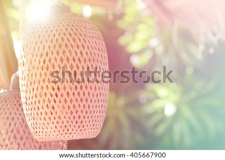 Wicker lamp shade against a background of garden, fill color filter pastel gradient tone. - stock photo