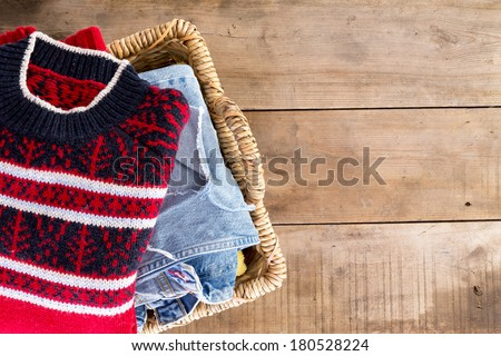 Wicker laundry basket filled with clean fresh washed winter clothes viewed from overhead standing at an angle on rustic wooden boards with copy space on the right - stock photo