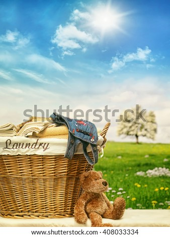 Wicker laundry basket with clothes against a blue sky - stock photo